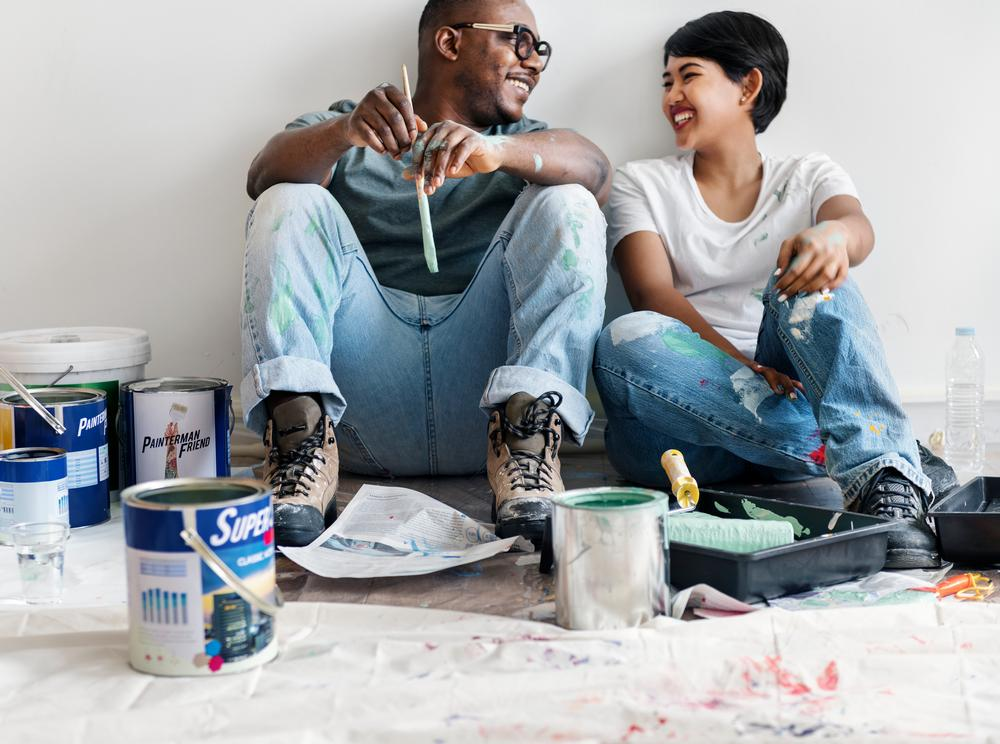 man-and-woman-smiling-while-painting-home-renovation